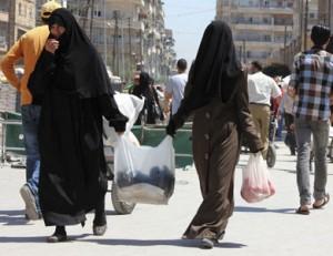 امرأتان سوريتان تتوجهان لعبور الحاج في منطقةٍ تشهد اشتباكات