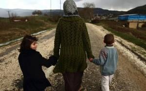 امرأة سورية نازحة مع طفليها