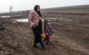 امرأة سورية نازحة حامل مع طفلتها