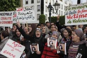 """نساء من مختلف مناطق المغرب يرفعن لافتات احتجاجا على العنف ضدّ المرأة، الرباط، 24 نوفمبر/تشرين الثاني 2013. كُتب على احدى اللافتات """"في ذكرى جميع النساء ضحايا العنف"""".  © 2013 Reuters"""