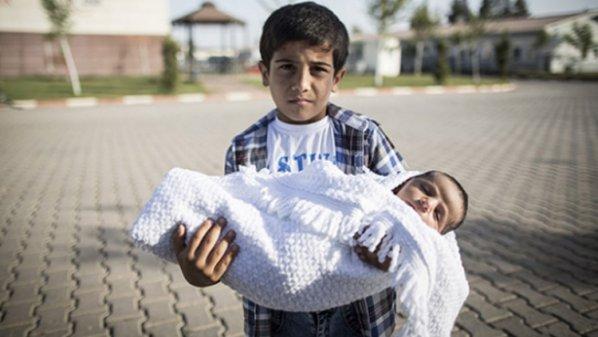 طفل رضيع مولود في تركيا يحمله أخاه الأكبر (أ ف ب)