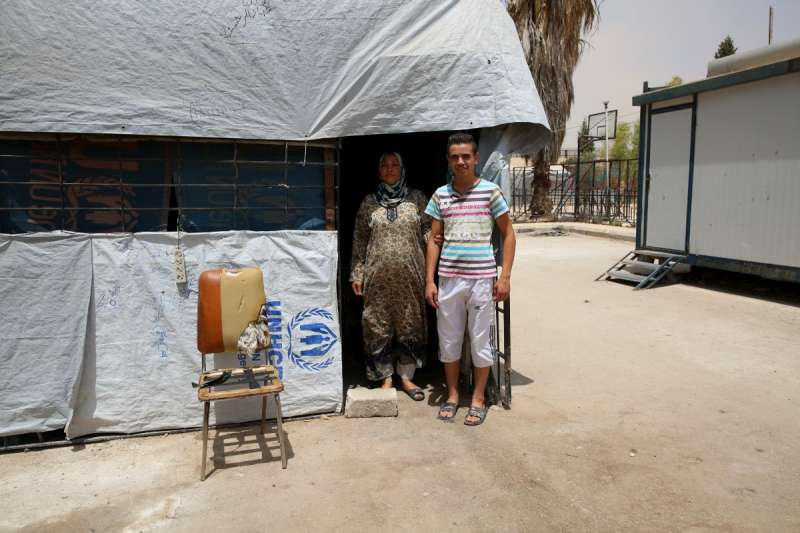 أم عبد الوهاب مع ابنها البكر ماهر أمام الكشك الصغير الذي أسسته لكسب العيش داخل مركز إيواء خان دنون في مدينة الكسوة بريف دمشق/UNHCR