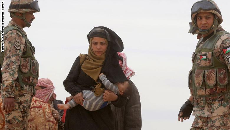 لاجئة سورية تحمل طفلاً وتمر بين عناصر الجيش الأردني بعد وصولها من سوريا/ أ ف ب