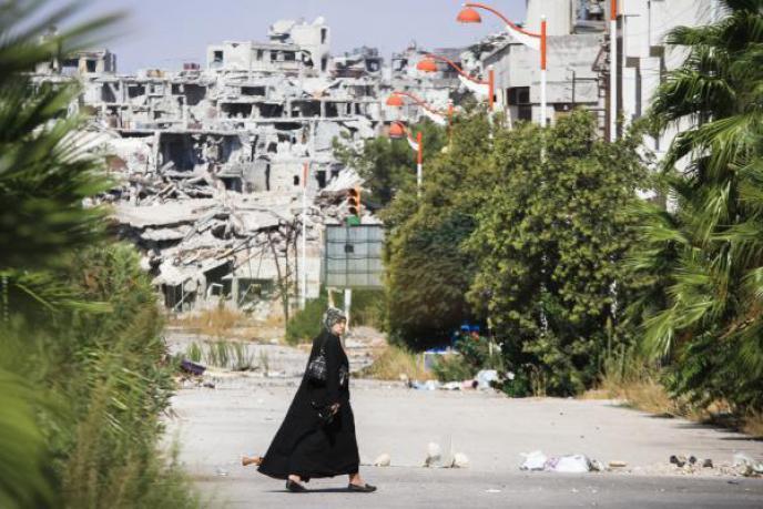 امرأة سورية تعبر قرب أحد المناطق التي دمرتها الحرب في سوريا/ راديو روزنة