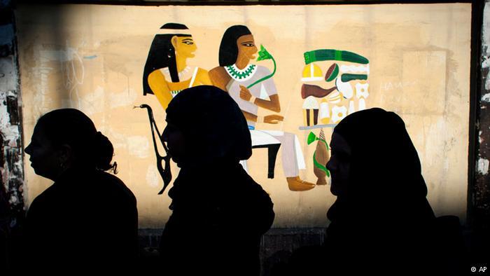 نساء مصريات أمام لوحة فرعونية/ AP