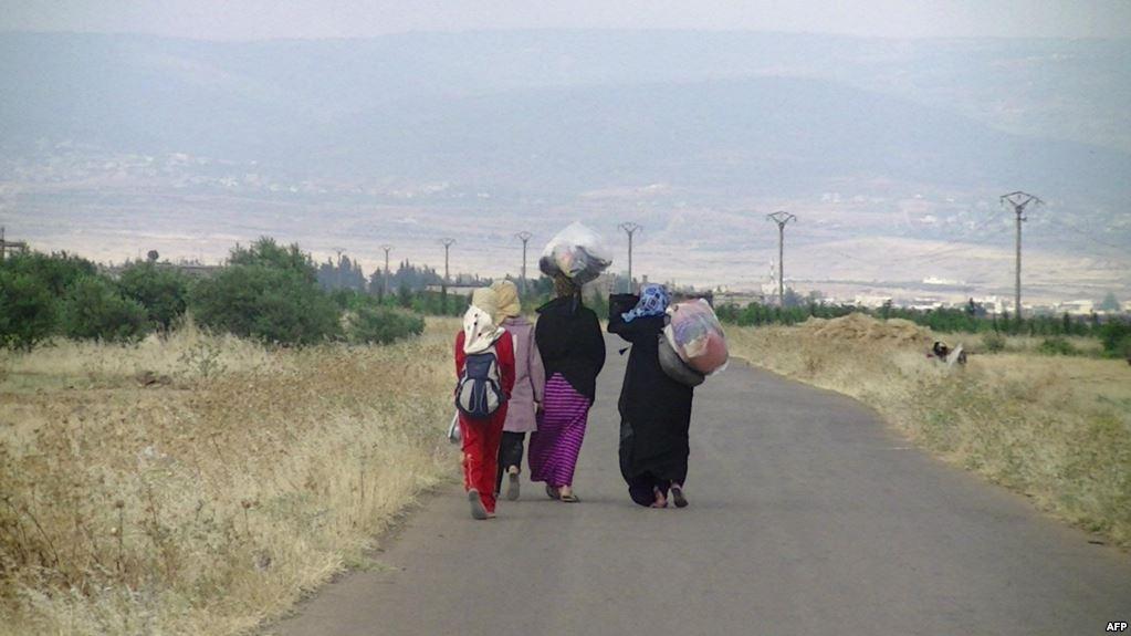 لاجئات سوريات يحملن أمتعتهن على رؤوسهن/ أ ف ب