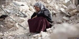 أم سورية تجلس فوق أنقاض منزلها المدمّر/ أرشيف