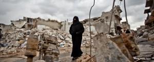 إمرأة بجانب أنقاض بيتها في حلب