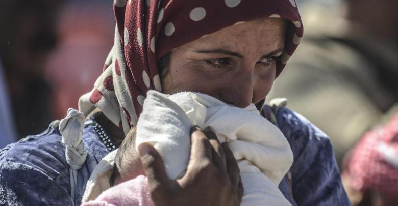 إمرأة سورية لاجئة تحتضن طفلها