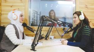 المذيعة غزالة حسو (يمين) ودلدا حج يوسف (يسار) وخلفهما المخرجة سيوان يوسف يعملنّ في إذاعة «جين» وهي أول تجربة كإذاعة نسائية/ الشرق الأوسط