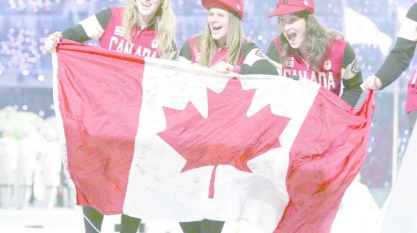 كنديات يحملن علم بلدهن (أ.ب)