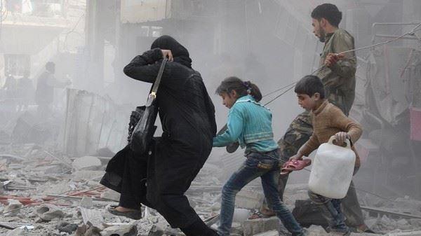 امرأةٌ تركض مع أطفالها لتفادي القصف والغارات في الغوطة/ انترنت