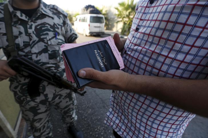 عنصر من الأمن العام يقف قرب سائق حافلة يحمل جوازات وبطاقات مغادرة لسوريين وافدين على لبنان. © 2015 رويترز