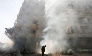 سوريٌّ يقف وسط منطقةٍ تعرّضت للقصف/ أرشيف