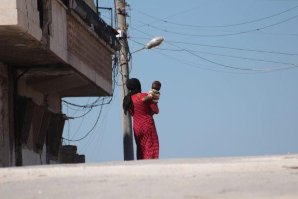 امرأة سوريّة من إدلب تحمل طفلها/ IWPR