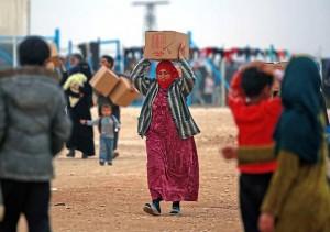 نازحة/ لاجئة سوريّة تحمل سلّةً إغاثية  (أرشيف)