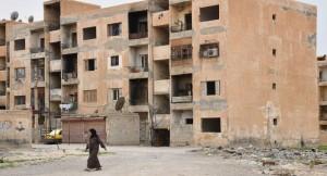 امراة سورية تسير بجوار بناءٍ تعرّض للقصف/ 2017