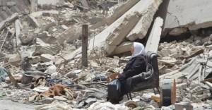 مخيم اليرموك 2018، سيدة سورية تنظرُ إلى بقايا منزلها