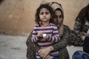 تحمل امرأة طفلة بينما تصل الأسر النازحة من رأس العين إلى تل تمر، بعد أن فرّت من العنف المتصاعد/ المصدر: يونيسيف