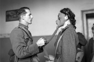 في هذه الصورة التي التقطت يوم 26 نوفمبر 1939، يشرح كبير الأطباء في الصليب الأحمر دينزلر لإحدى المتطوعات في منظمة الخدمة العسكرية للمرأة السويسرية كيفية ارتداء قناع غاز وضبطه. وقد تم الاعتراف بالمنظمة رسميًا في أبريل 1940.