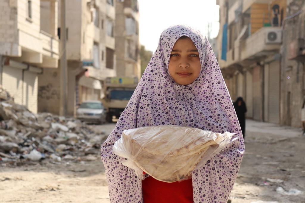 فتاة في حي الصالحين الفقير في حلب تحمل الخبز الذي يقوم بتوزيعه برنامج الأغذية العالمي/ WFP