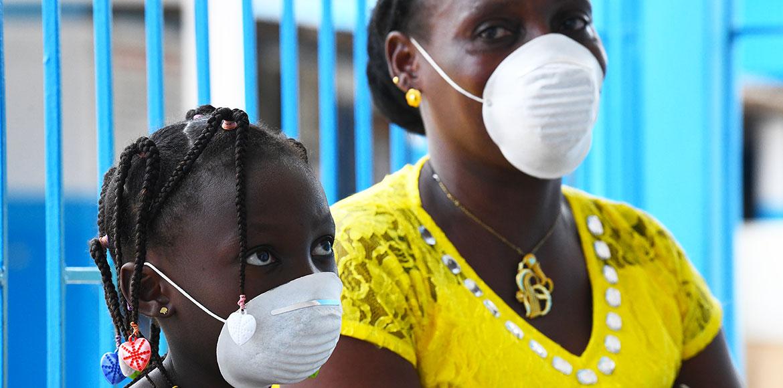 أم وابنتها ترتديان أقنعة على الوجه للوقاية من فيروس كورونا في أحد مراكز الرعاية الصحية في أبيدجان، كوت ديفوار