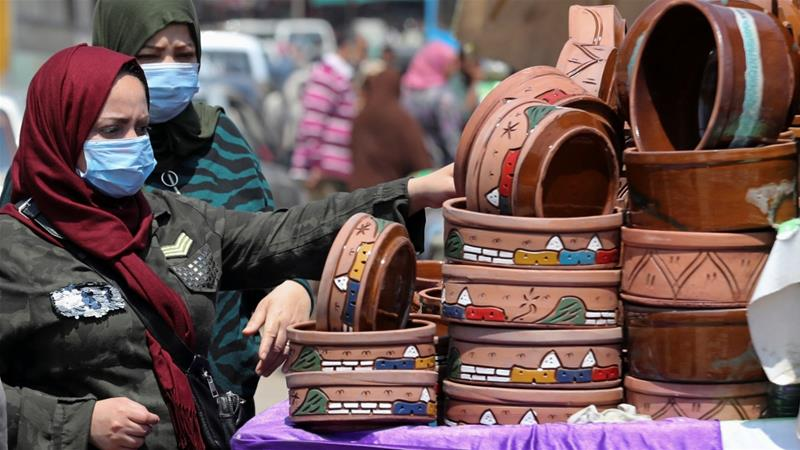 Women shop at a market wearing protective face masks amid concerns over COVID-19 in Cairo, Egypt on April 12, 2020 [Mohamed Abd El Ghany/Reuters]