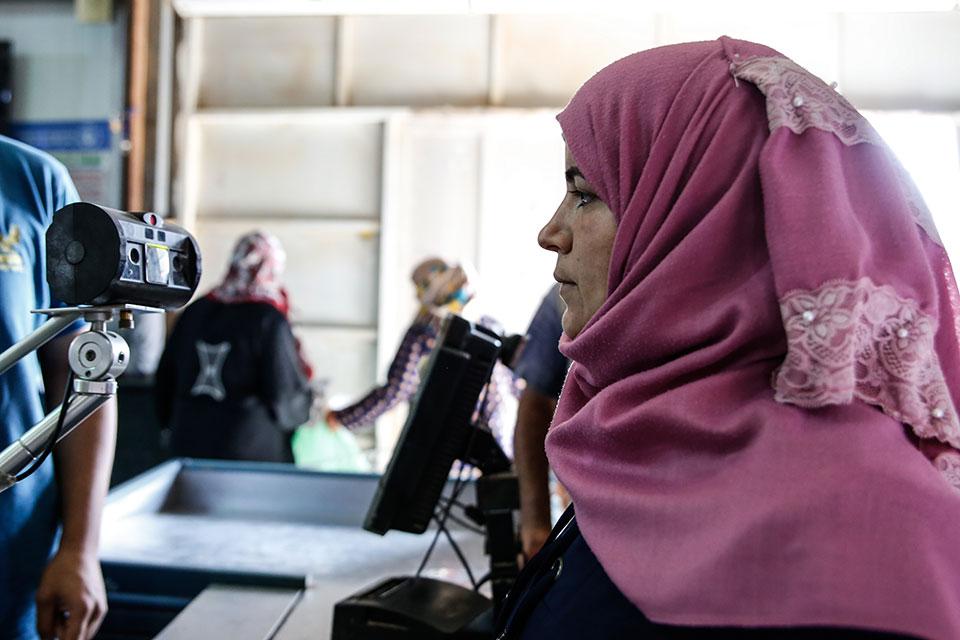 تقوم مستفيدة من هيئة الأمم المتحدة للمرأة بفحص عينيها، مما يسمح لها بشراء الحاجيات من سوبر ماركت في مخيم الأزرق للاجئين، الأردن. الصورة: هيئة الأمم المتحدة للمرأة/لورين روني