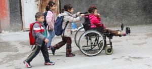 UNICEF/Can Remzi Ergen طفلة لاجئة من ذوي الإعاقة تجلس على كرسي متحرك تساعدها أختها بينما تتوجه هي وأشقاؤها إلى المدرسة في تركيا.