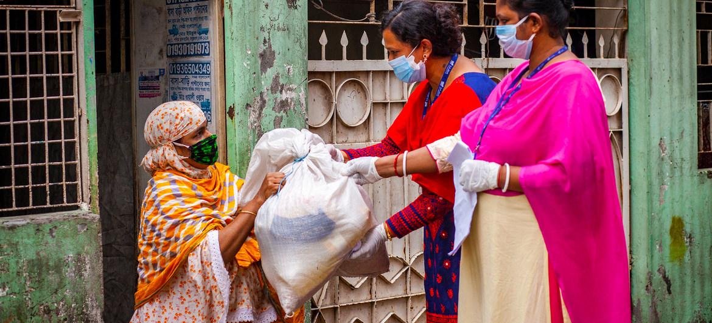 سيدتان تعملان في مجال التنمية تقدمان مساعدات الإغاثة لسيدة خلال جائحة كوفيد-19 في دكا ببنغلاديش.