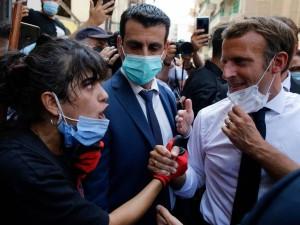ماكرون وامرأة لبنانية خلال زيارته لبيروت عقب الانفجار