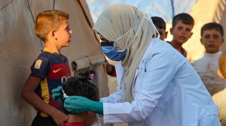 طبيبة سورية ترشد الأطفال على كيفية ارتداء قناع الوجه في ظلّ جائحة كورونا/ أ ف ب