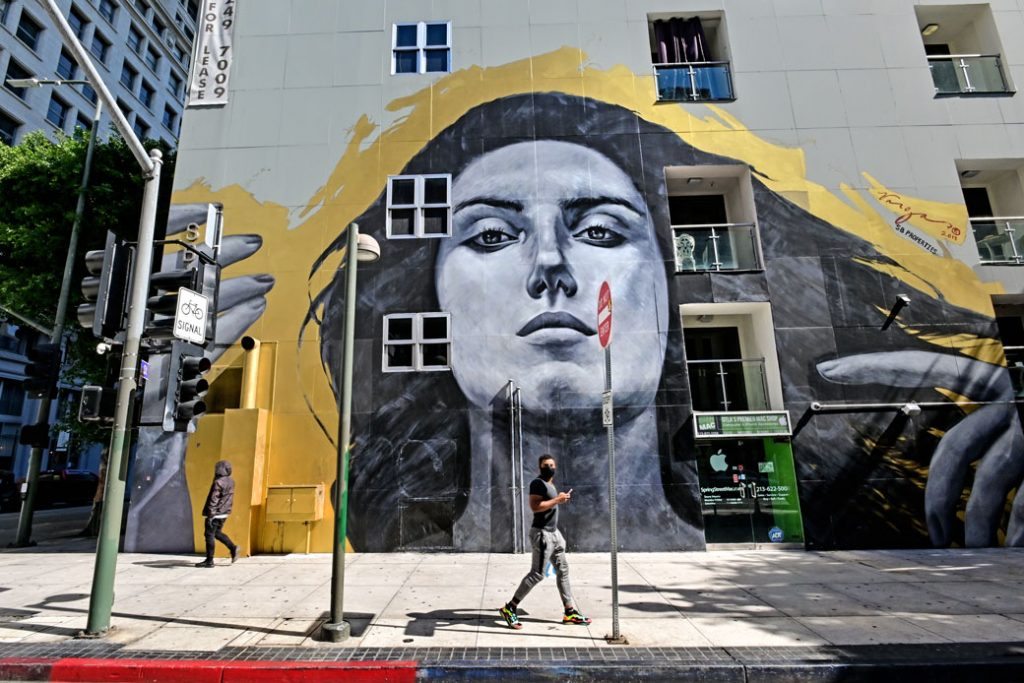 A man with mask walks past a mural of a woman on an empty street due to the COVID-19 outbreak in Los Angeles, March 2020/ Getty Image