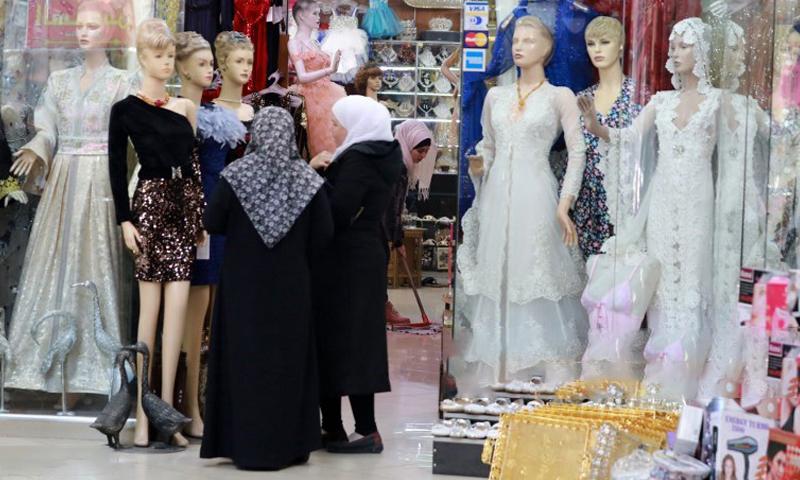 نساء سوريات ينظرن إلى فساتين معروضة أمام متجر لبيع الملابس في سوق الحميدية في المدينة القديمة بالعاصمة السورية دمشق - 3 كانون الأول 2019 (AFP)